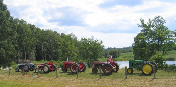 Five tractors in line in front of pond